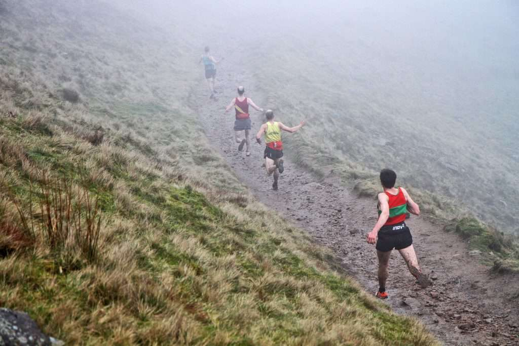 Tom Addison in the lead as elite runners blast downhill at full speed. Photo by Andy Holden