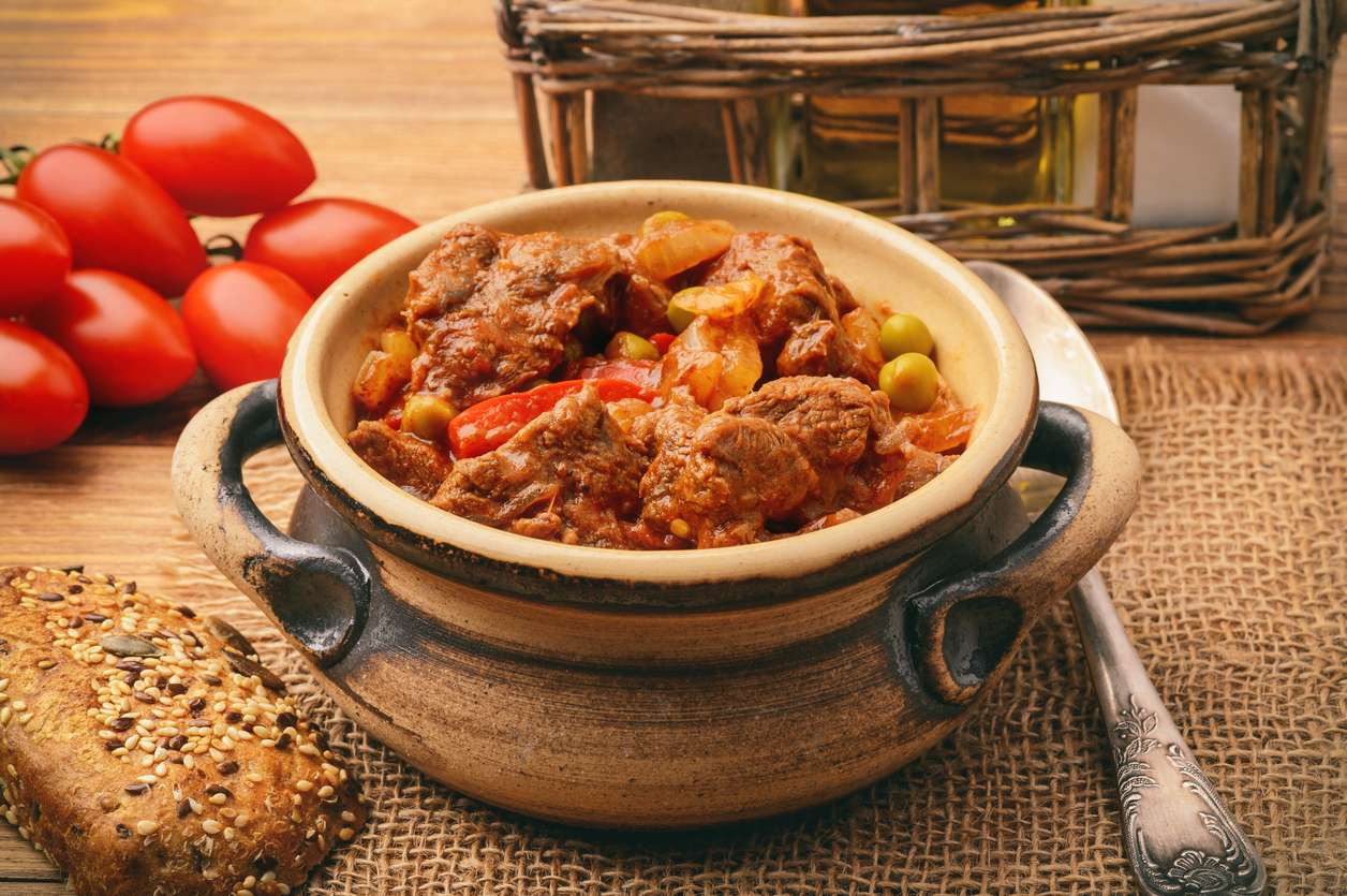 Goulash from venison meat on brown wooden background.