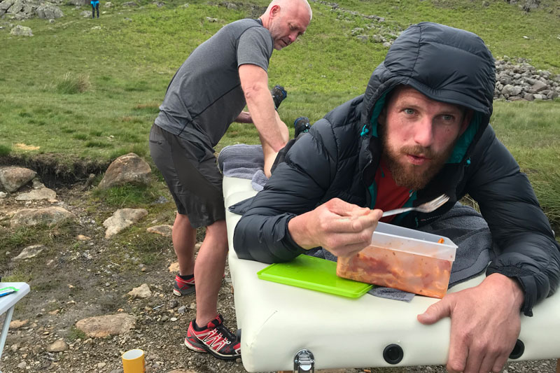 Paul grabbing a quick bite of pasta, courtesy of Neil Talbott, whilst being 'treated' to an impromptu physio session by Adam Smith at Hardknott Pass.